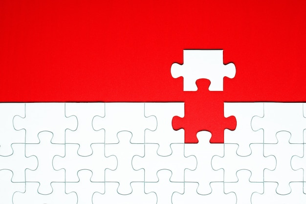 Weiße puzzleteile auf einem roten hintergrund getrennt