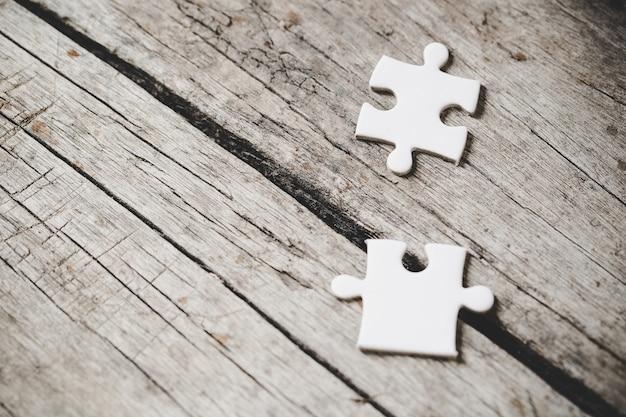 Weiße puzzleteile auf holz