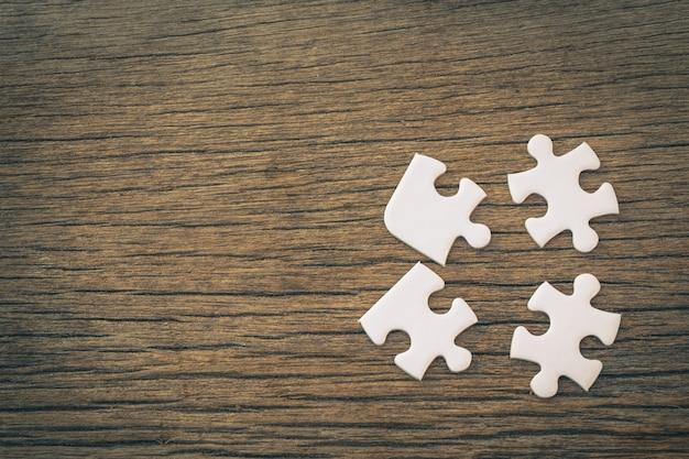 Weiße puzzleteile liegen auf einem hölzernen hintergrund