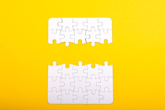 Weiße puzzleteile lokalisiert auf gelbem hintergrund