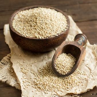 Weiße quinoa in einer schüssel mit einem holzlöffel nahaufnahme