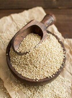 Weiße quinoa mit einem holzlöffel und einer schüssel