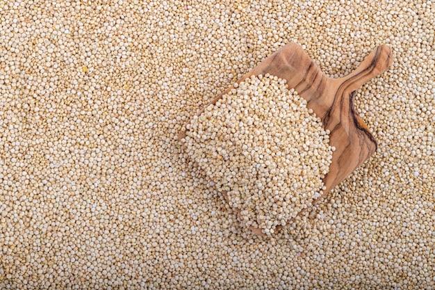 Weiße quinoaoberfläche mit einem holzlöffel, nahaufnahme