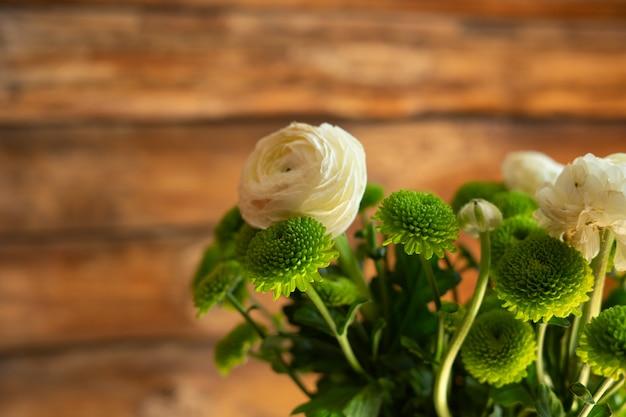 Weiße ranunculi und grüne frühlingsblumen auf hölzernem hintergrund.