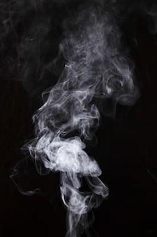 Weiße rauchfragmente auf schwarzem hintergrund