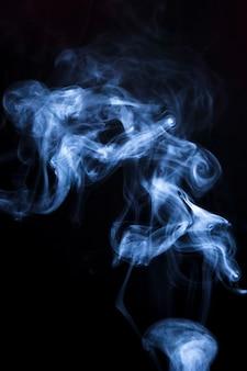 Weiße rauchzusammenfassungswellen auf schwarzem hintergrund