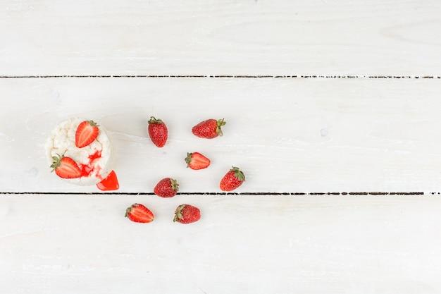 Weiße reiskuchen der draufsicht mit erdbeeren auf weißer holzbrettoberfläche. horizontal