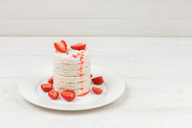 Weiße reiskuchen der hohen winkelansicht auf teller mit erdbeeren auf weißer holzbrettoberfläche.