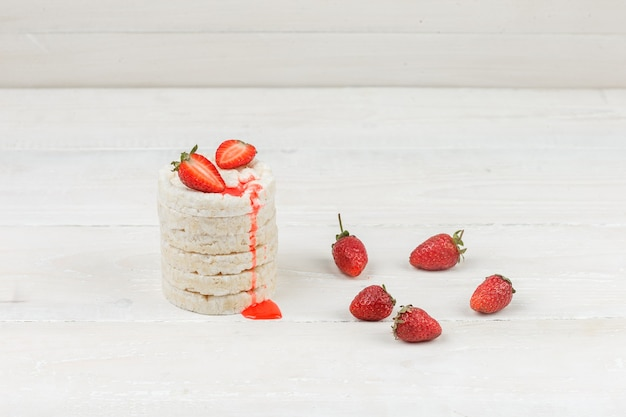 Weiße reiskuchen der nahaufnahme mit erdbeeren auf weißer holzbrettoberfläche. horizontal