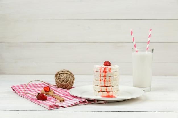 Weiße reiswaffeln mit hoher winkelansicht auf teller mit erdbeeren, baisers, seilschlaufe und milch auf weißer holzbrettoberfläche.