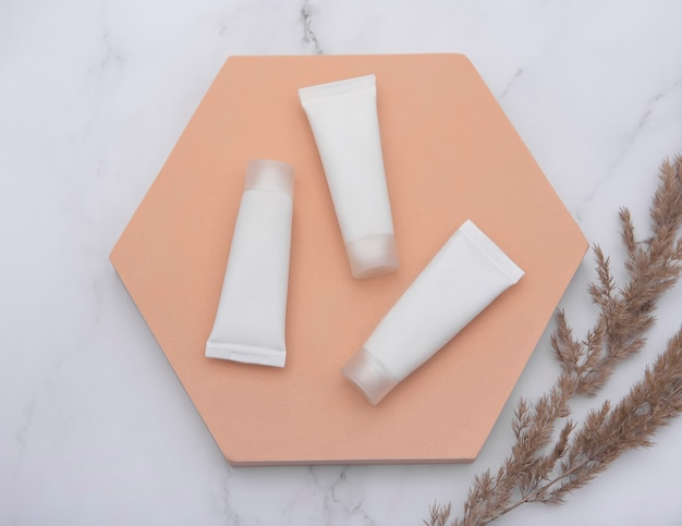 Weiße röhrchen der creme auf einem marmorhintergrund und einem dekorativen zweig mit weißen blättern