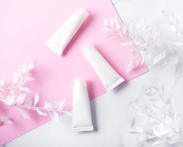 Weiße röhrchen mit sahne und dekorativem zweig mit weißen blättern