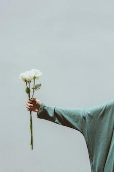 Weiße rose in einer hand mit grauem wandbeton auf dem hintergrund