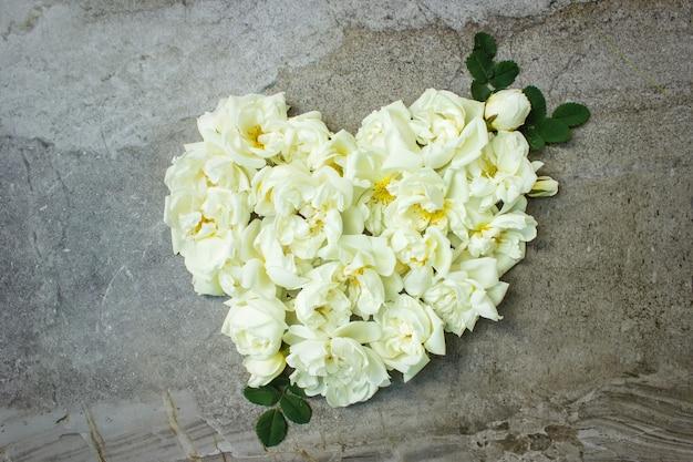 Weiße rose in form eines herzens, das aus einem glas auf hölzernem hintergrund kopienraum für text verschüttet