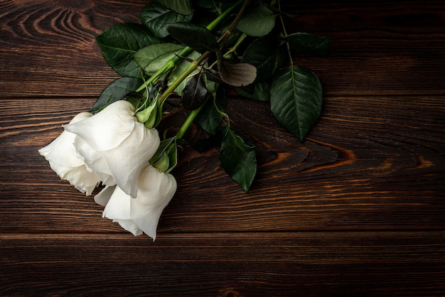 Weiße rosen auf dunklem holztisch.