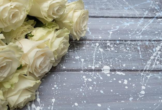 Weiße rosen auf einem grauen hölzernen hintergrund. kopieren sie platz.