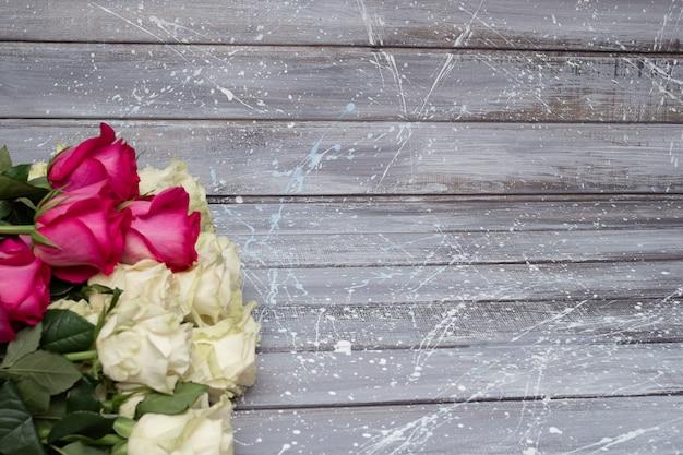 Weiße rosen auf einem grauen und rosa hintergrund.