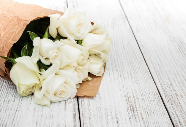 Weiße rosen auf einem holztisch