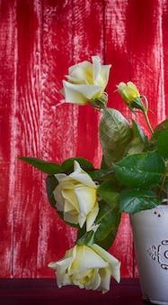 Weiße rosen auf einem roten hölzernen