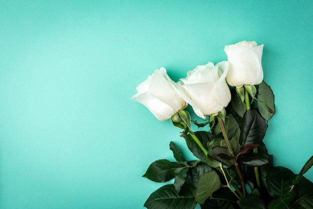 Weiße rosen auf grünem tisch.