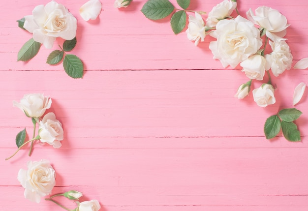 Weiße rosen auf rosa hölzernem hintergrund