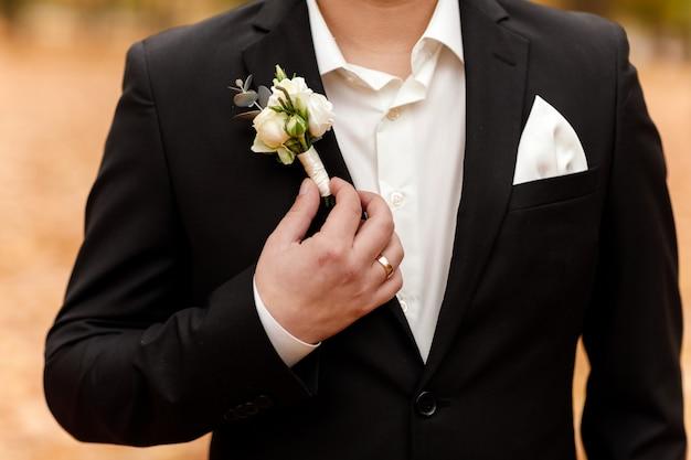 Weiße rosen blühen im knopfloch, der bräutigam trägt einen dunklen anzug und ein weißes hemd. hochzeitszeremonie, eleganter anzug. outfit des tages.