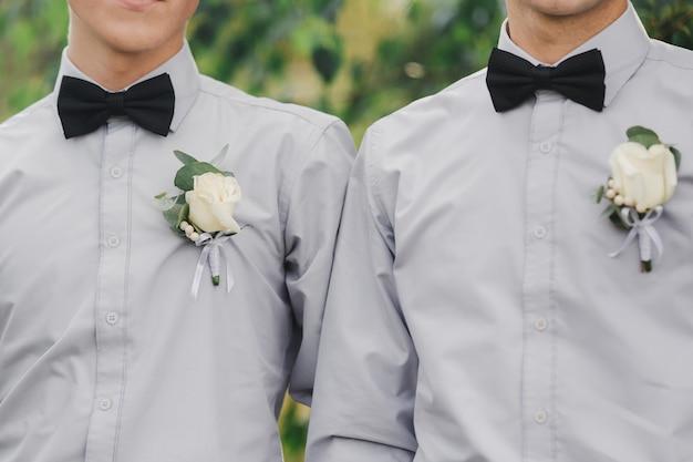 Weiße rosen blühen im knopfloch, zwei bräutigamfreunde tragen ein graues hemd und eine fliege. hochzeitstag. outfit des tages.
