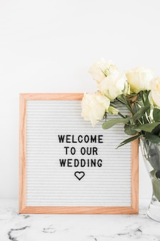 Weiße rosen blühen im vase und willkommensbrett für die heirat