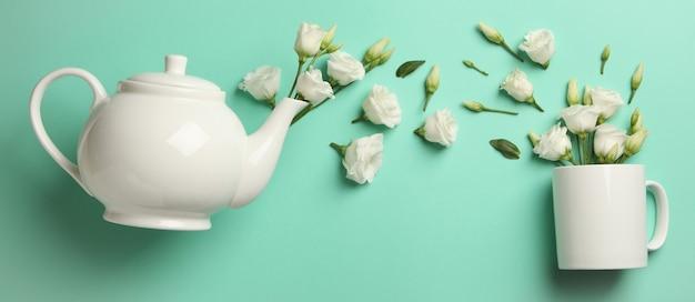 Weiße rosen, die von einer teekanne in eine tasse auf einem minzhintergrund gießen