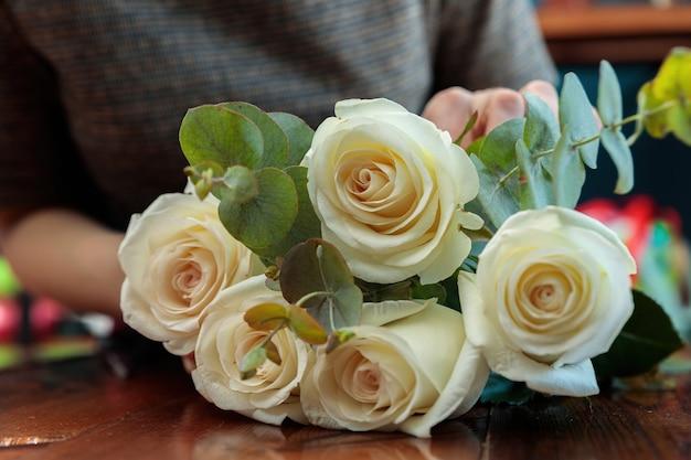 Weiße rosen liegen auf einem holztisch. die hände des floristen machen einen strauß.