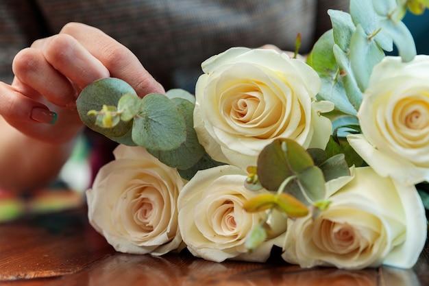 Weiße rosen liegen auf einem holztisch
