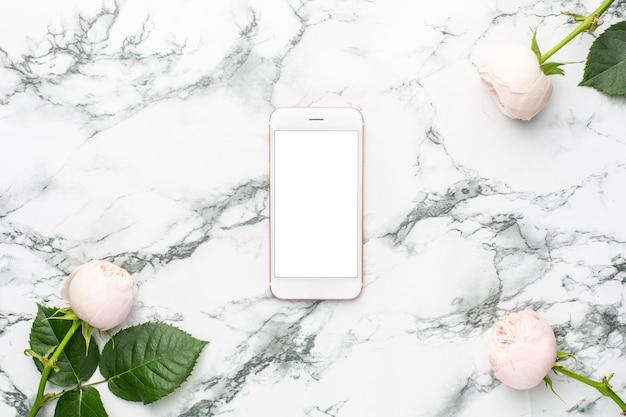 Weiße rosen mit handy auf weißem und schwarzem marmorhintergrund mit copyspace