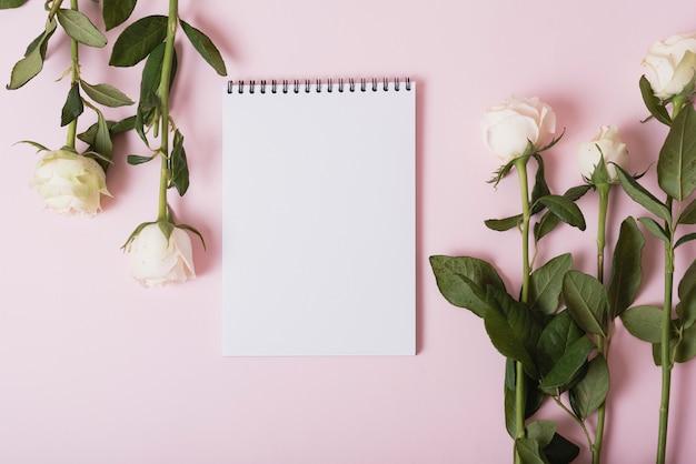 Weiße rosen mit leerem gewundenem notizblock gegen rosa hintergrund