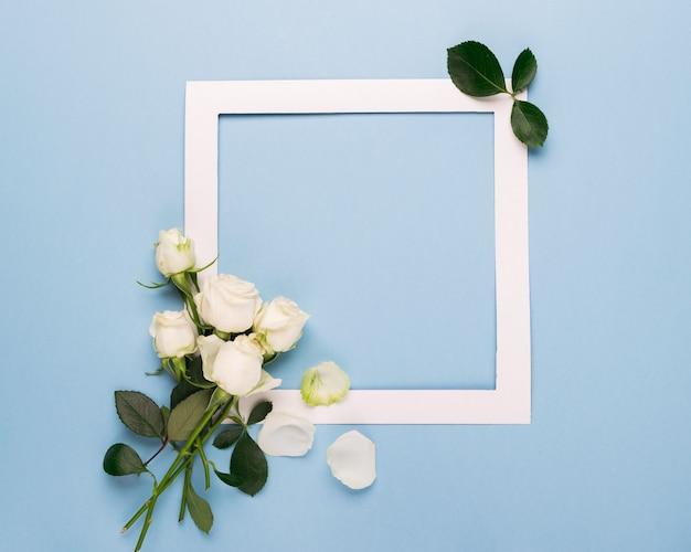 Weiße rosen und ein weißer papierrahmen sind mit frischen blättern auf blauem grund verziert