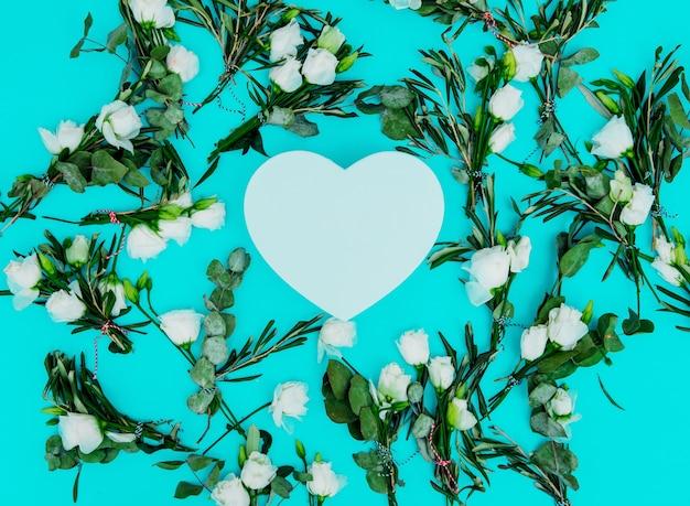 Weiße rosen und herzform auf grünem hintergrund. ansicht von oben