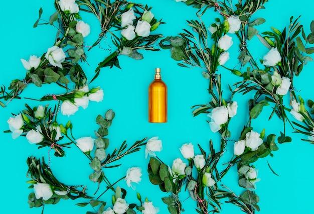 Weiße rosen und parfümflasche auf grünem hintergrund. ansicht von oben