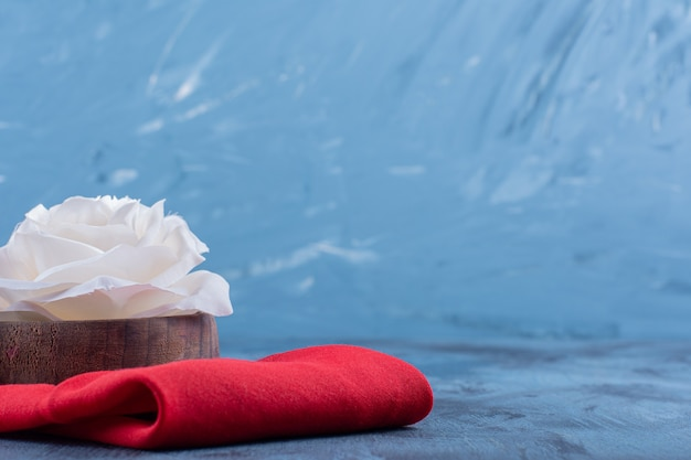Weiße rosenblüte auf roter tischdecke auf blauem.