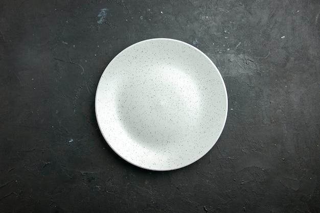 Weiße runde platte der draufsicht auf dunklem tisch mit kopierplatz