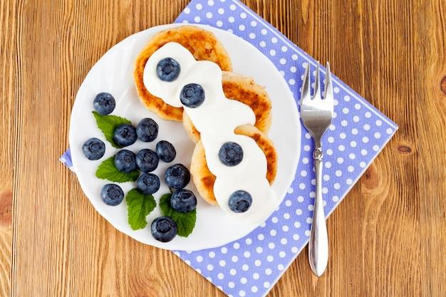 Weiße runde platte mit leckeren käsekuchen, sauerrahm und blaubeermarmelade, nahansicht oben