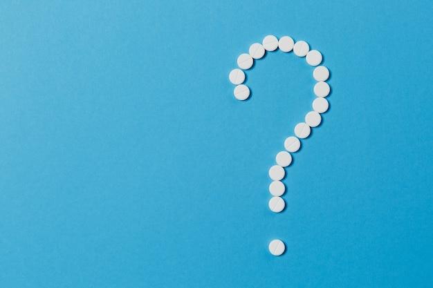 Weiße runde tabletten der medikamente, die in fragezeichenform einzeln auf blauem hintergrund angeordnet sind