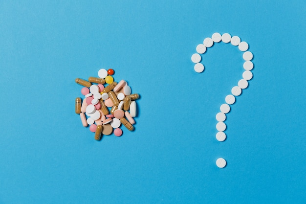 Weiße runde tabletten der medikamente, die in fragezeichenform lokalisiert auf blauem farbhintergrund angeordnet sind. bündel bunte pillen, buntes zeichen. konzept der gesundheit, behandlung, wahl, gesunder lebensstil.