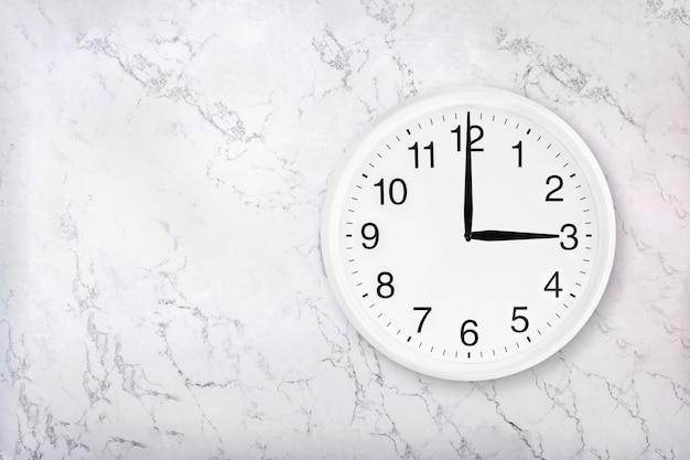 Weiße runde wanduhr auf weißem marmorhintergrund