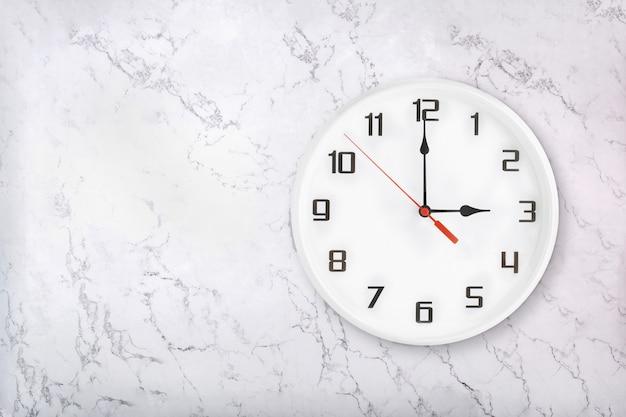 Weiße runde wanduhr auf weißem natürlichem marmorhintergrund. drei uhr