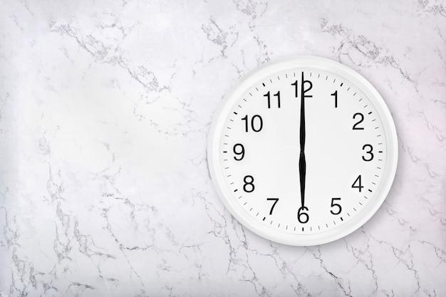 Weiße runde wanduhr auf weißem natürlichem marmorhintergrund. sechs uhr