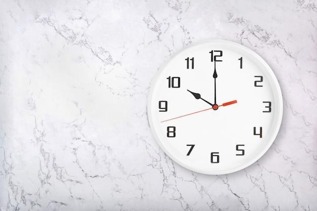 Weiße runde wanduhr auf weißem natürlichem marmorhintergrund. zehn uhr