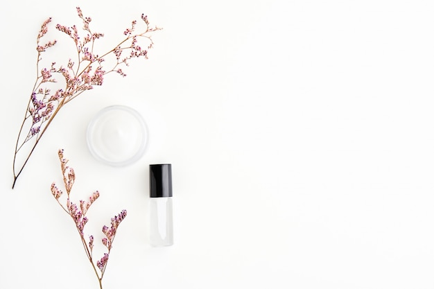 Weiße sahneflasche platziert und blumen, blanko-label-paket für mock-up