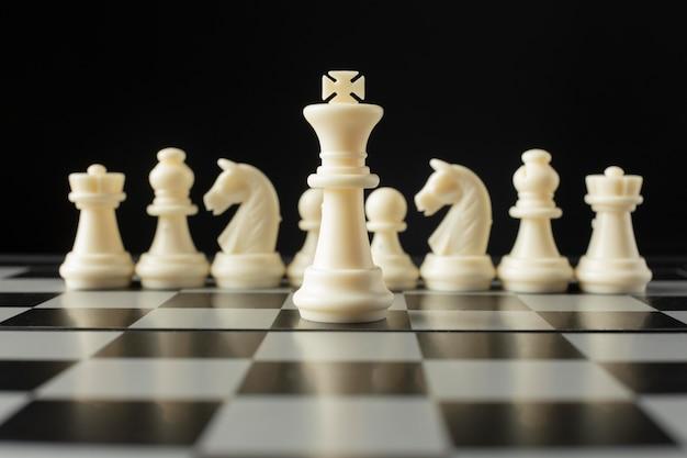 Weiße schachfiguren auf schachbrett. könig konzept