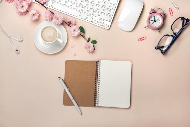 Weiße schale mit cappuccino, kirschblüte blüht, tastatur, wecker, notizbuch auf einem pastellrosahintergrund
