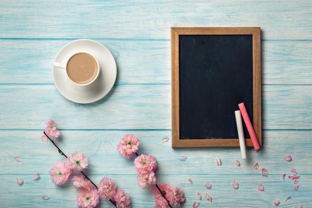 Weiße schale mit cappuccino, kirschblüte-blumen und kreidebrett auf einem blauen holztisch.