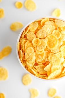 Weiße schale mit den goldenen corn flakes lokalisiert auf weiß